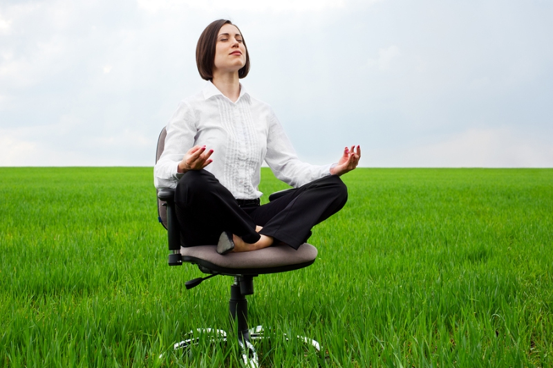 businesswoman sitting in lotus position on green field